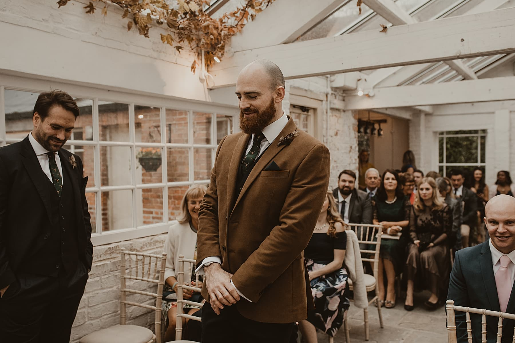 Groom waiting at the end of the aisle